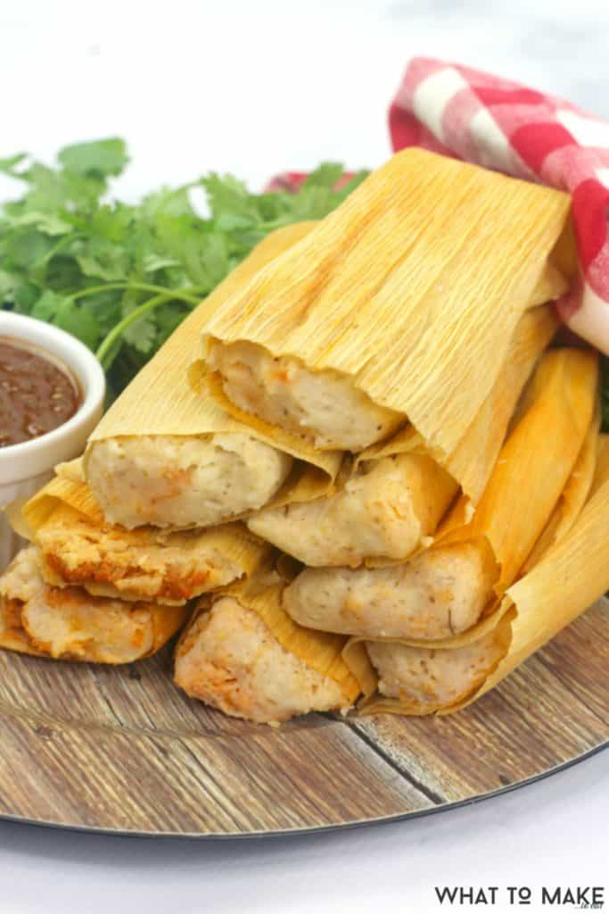 A stack of pork tamales, that have been cooked in a pressure cooker, sitting on a wooden platter.