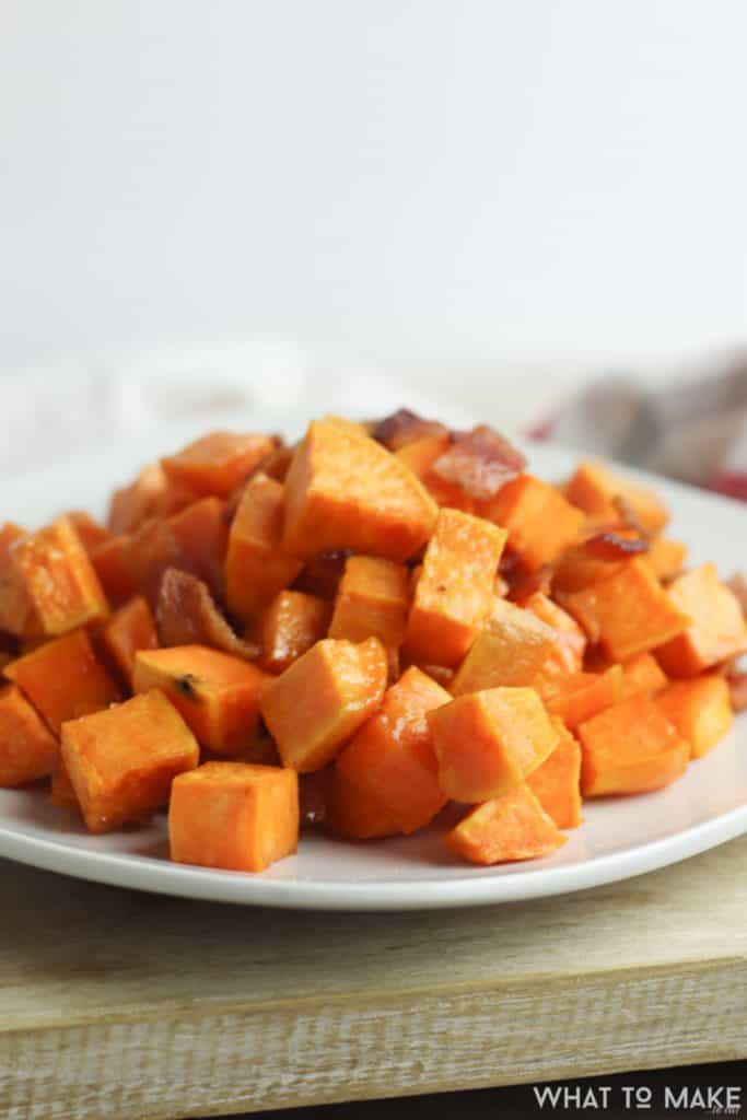 Plate of roasted diced sweet potatoes with bacon.
