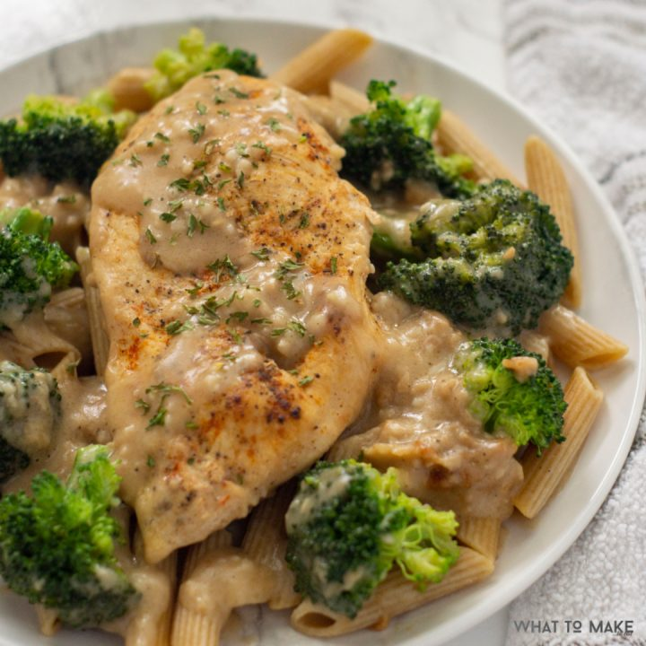 Plate of chicken breast and broccoli with a garlic cream sauce.