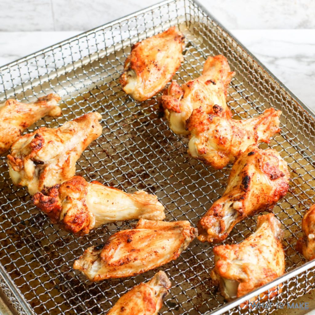 Image is an in process shot of air fryer bbq chicken wings.